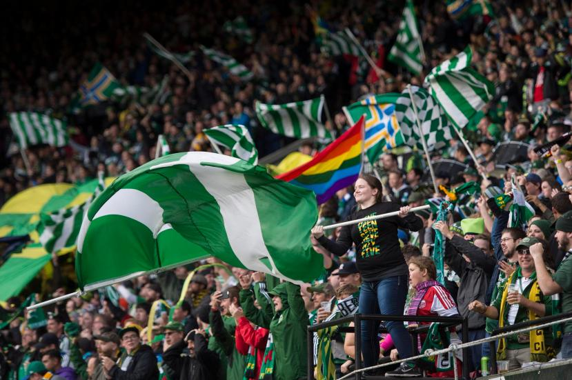 Portland Timbers fans celebrate after the Timbers scored a goal in a game against the Colorado Rapids during the first half of their MLS soccer game in Portland, Ore., Sunday, Oct. 25, 2015. (AP Photo/Troy Wayrynen)